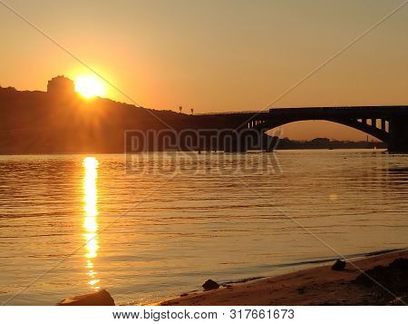 Sunset Over Dnipro River, Ukraine. Beautiful Sunset Background With Bridge And Calm Water