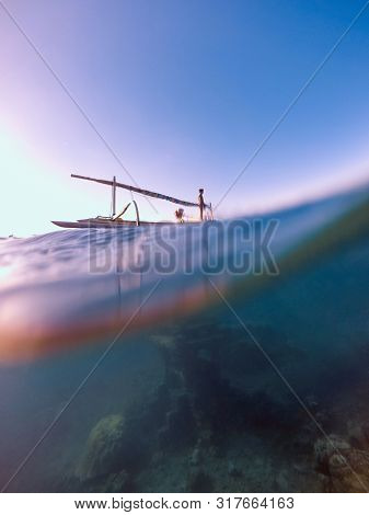 Ship sailing over temple ruins. Sunken building. Treasure. Ocean underwater dome. Under water sea. Splitted by waterline. Half water half sky.  Over and under view of ocean. Fisherman boat. Caribbean.