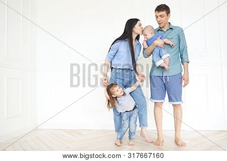 Happy Young Parents With Their Adorable Little Kids At Home Having Fun Together