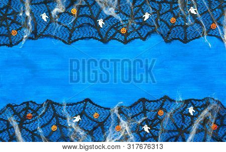 Halloween background with spider web, spiders and smiling jack and ghosts decorations as symbols of Halloween on the dark blue wooden background. Halloween holiday concept