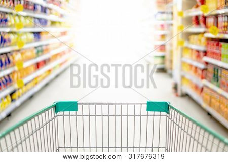 Empty Shopping Cart Or Pushcart In Supermarket Aisle. Buying Goods Or Products In Grocery Store. Sho