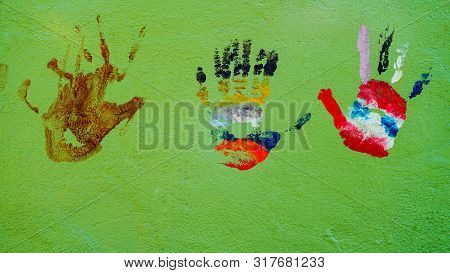 Colored Kids Handprints On Green Background, Multicolored Kids Handprints.