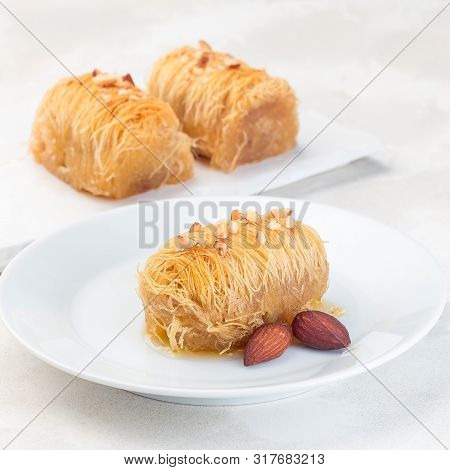 Greek Pastry Kataifi With Shredded Filo Dough Stuffed With Almond Nuts, In Honey Syrup, On A White P