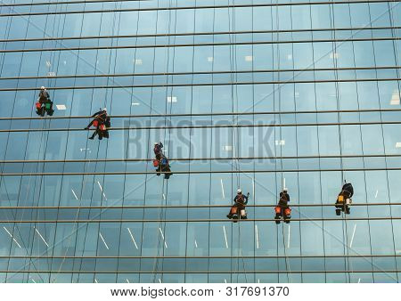 Group Of Workers Cleaning Windows Service On High Rise Building. Window Washers Industrial Climbers