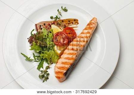 Grilled Salmon Steak Fresh Vegetables On A White Plate