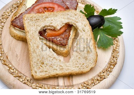 Healthy sandwich made with whole grain bread, cheese, and salami slices.
