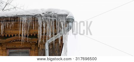 Frozen mysterious mansion with downnpipe and icicles on the roof, top floor antique house. Icy weather winter scene. copy space poster