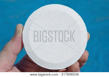 Hand Holding A Pool Chlorine Tablet. Chlorine For The Pool Water Treatment. Tablet With A Rounded Sh