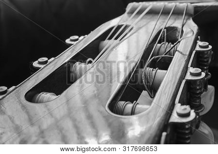 Headstock Of An Acoustic Guitar. Details Of The Head With The Nylon Strings Coiled On The Tuning Peg
