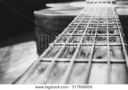 Perspective Photo Of The Neck Of An Old Acoustic Guitar And The Body Unfocused On The Background. Fo