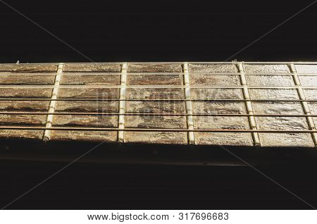Isolated Neck Of A Acoustic Guitar On The Horizontal. Details Of The Worn Out Wooden Neck. Neck Of A