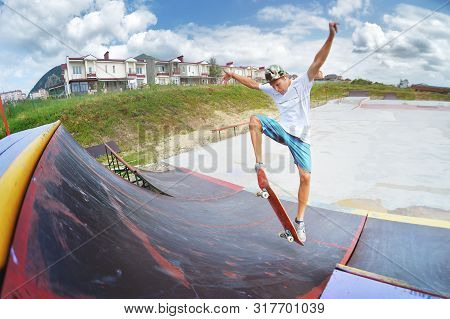 A Teenager In Shorts And A Cap Does An Allie Stunt On A Ramp In A Skate Park In A Residential Area I