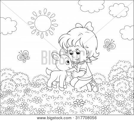 Happy Little Girl Playing With A Small Kid Among Wildflowers On Grass Of A Summer Field On A Sunny D