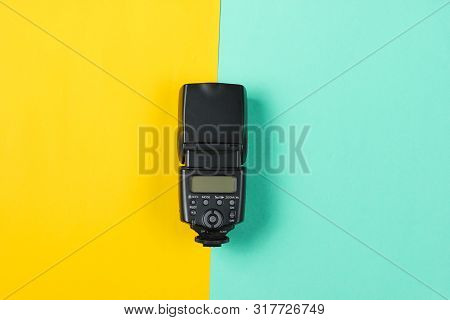 Camera Flash On Colored Paper Background. Top View