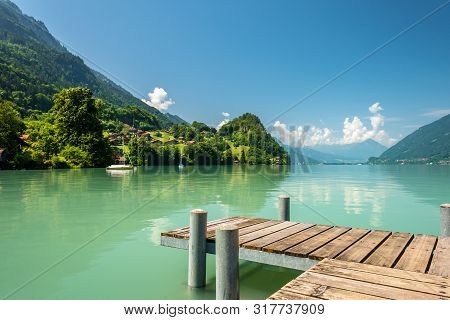 View Of Brienz Lake With Clear Turquoise Water. Wooden Pier. Traditional Wooden Houses On The Shore