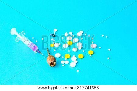 Pills And Medical Syringe On Blue Background. Painkiller Or Narcotic  Prescription For Treatment Med
