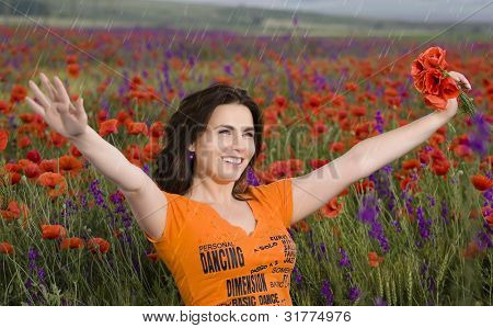 beautiful girl on a field with poppies while raining