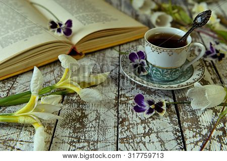 Open Book Of Poetry, Old Cup Of Tea And Flowers On Table.  Vintage Still Life, Poetry And Literature