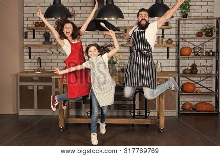Having Fun In Kitchen. Family Mom Dad And Little Daughter Wear Aprons Jump In Kitchen. Family Having