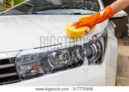 Woman Hand Wearing Orange Gloves With Yellow Sponge Washing Headlight Modern Car Or Cleaning Automob