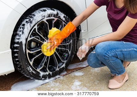 Woman Hand Wearing Orange Gloves With Yellow Sponge Washing Wheel Modern Car Or Cleaning Automobile.
