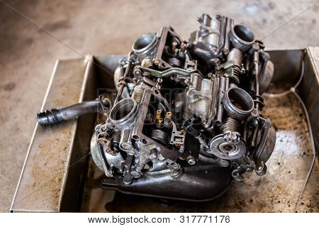 Maintenance And Clean The Carburetor Parts For The Fire Pump Old Motorcycle Engine. Close Up And Sel