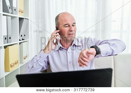 Middle-aged Businessman Sitting At Office Desk And Checking Time On His Smartwatch When Talking On P