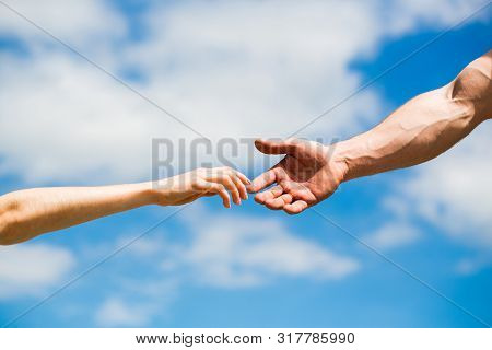 Hands Of Man And Woman Reaching To Each Other, Support. Hands Of Man And Woman On Blue Sky Backgroun