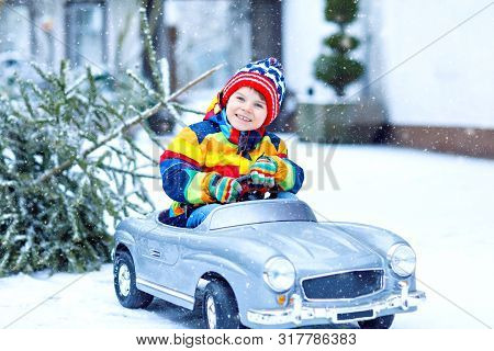 Funny Little Smiling Kid Boy Driving Toy Car With Christmas Tree. Happy Child In Winter Fashion Clot