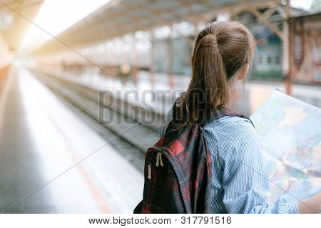 poster of Young woman traveler holding map while looking for some direction at train station for travel. Travel concept by train.