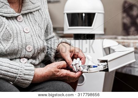 Autonomous Caregiver Robot Is Holding A Insulin Syringe, Giving It To An Senior Adult Woman In Her L