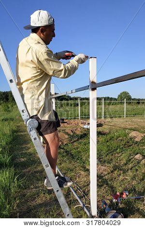 The Outdoor Master Is Standing On The Ladder And Removes Fence Measurements.