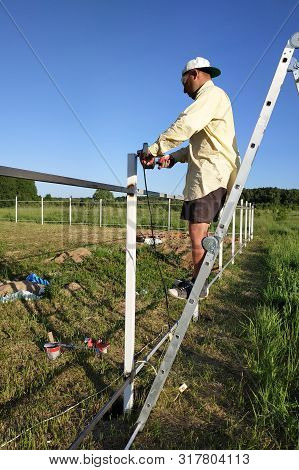 The Master Cuts The Remnants Of The Metal Profile Of The Fence With An Angle Grinder Standing On The