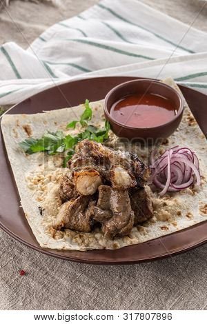 Shish Kebab On Lavash Bread With Red Onion And Tomato Sauce On Brown Plate On Tablecloth Side View