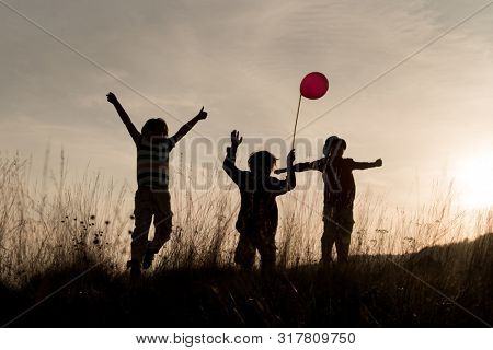 Happy children silhouette with balloon on sunset meadow