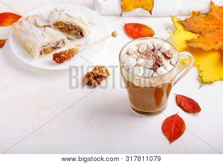 Autumn Composition With Cup Of Hot Drink, Delicious Apple Strudel   And Colorful Fall Leaves On Whit