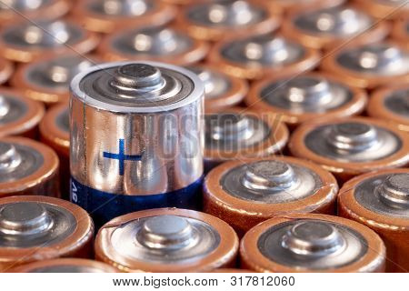 Multiple Used Aa Alkaline Batteries Are Seen Arranged In A Pile. Closeup Side View From The Plus Sid