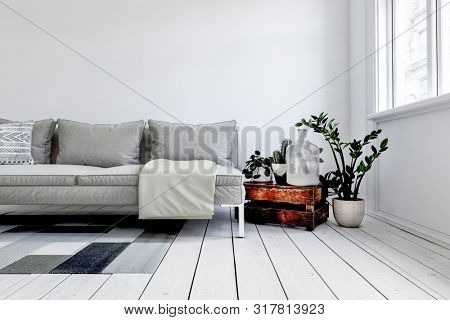 Digital render of modern grey couch in front of white wall next to rustic wood crate and small plant in pot. 3d rendering