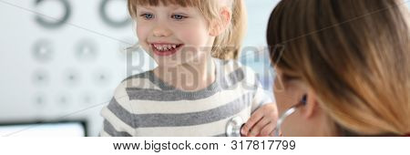 Female Doctor Working With Cute Smiling Little Girl At Her Office Portrait