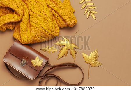 Brown Leather Women Bag, Orange Knitted Sweater, Golden Autumn Leaf On Brown Background Top View Fla