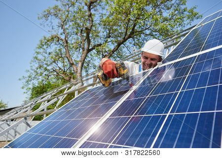 Professional technician working with screwdriver installing solar photo voltaic panel to high metal platform. Exterior solar system installation, cheap green ecological energy production concept. poster