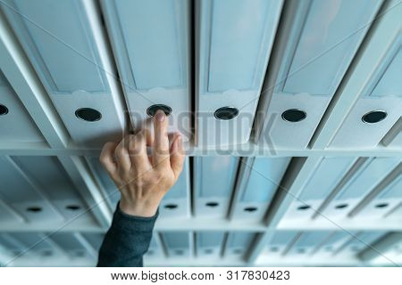 Businesswoman Browsing Through Ring Binder File Documentation Archives On The Shelf In Business Offi