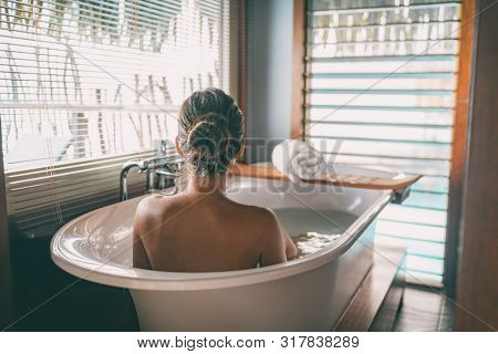 Luxury bath woman wellness spa relaxing soaking in warm water bathtub of hotel suite. poster
