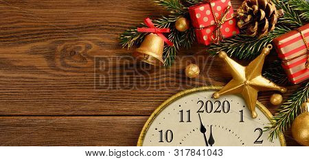 New Years 2020 Eve. Retro Style Clock With Christmas Decorations And Gifts On Brown Wooden Backgroun