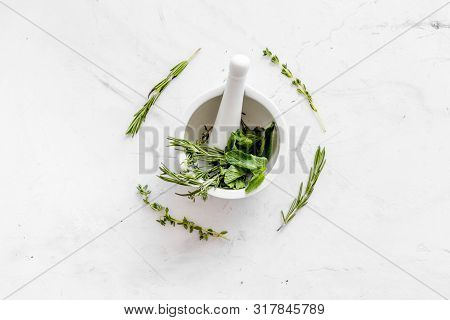 Homeopathy With Leaves And Healing Herbs For Making Oil On White Marble Background Top View