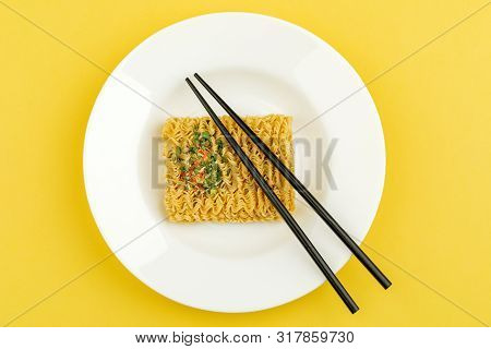 A Plate Of Noodles On A Yellow Background. Top View