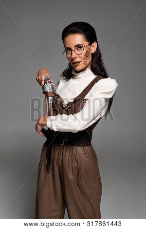 Attractive Steampunk Woman Holding Vintage Pistol On Grey