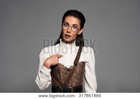 Front View Of Surprised Steampunk Woman Pointing With Finger At Herself Isolated On Grey