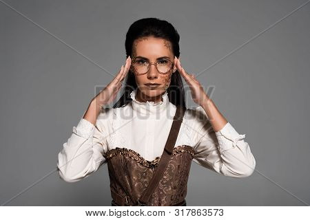 Front View Of Steampunk Woman With Makeup Touching Glasses Isolated On Grey