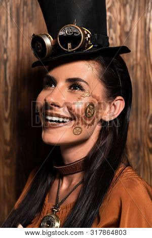 Cheerful Steampunk Woman With Makeup Looking Up And Smiling On Wooden